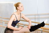 Ballet dancer stretches herself near barre and mirrors in the dancing hall