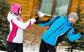 Young couple having fun outdoors during winter vacations and playing at snowballs
