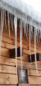 Wooden House With Big Icicles On Snow-covered Roof