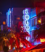 People Enjoy Nightlife At The Colorful Ocean Drive By Night With View To Colony Hotel