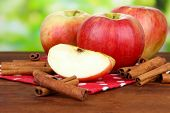 image of cinnamon sticks  - Ripe apples with with cinnamon sticks  on  wooden table - JPG