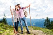 Hiking - Young couple standing on mountain summit in the Bavarian Alps enjoying the panorama in their leisure time or vacation