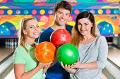 Young people or friends, man and women, playing bowling with a ball in front of the ten pin alley, t