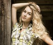 Portrait of Blonde Woman at the Wooden Background
