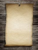 old wanted paper or parchment pinned by nail to grunge wooden background