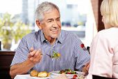 Senior man talking to woman while eating in a restaurant