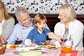 Happy grandparents feeding grandson at family dinner table
