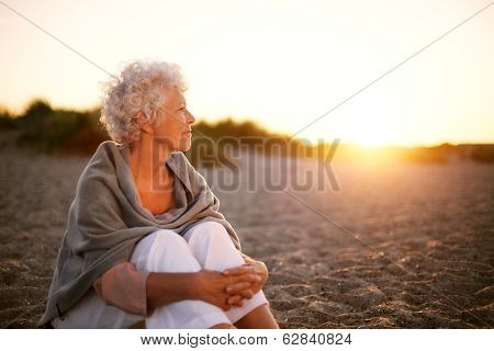 Old Woman Sitting On The Beach Looking Away At Copyspace poster