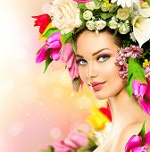 Spring Woman. Beauty Summer model girl with colorful flowers. Flowers Hair Style. Beautiful Lady with Blooming flowers on her head. Nature Hairstyle. Holiday Fashion Makeup. Make up