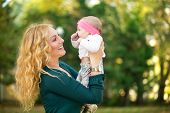 Portrait of cheerful mom with baby outdoor