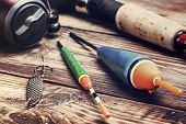 stock photo of fly rod  - fishing tackle on a wooden table. toned image