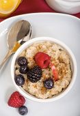Delicious bowl of freshly made steal cut oatmeal served with fresh blackberries, blueberries, raspbe
