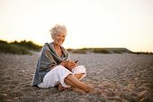 Senior Caucasian Woman With Cell Phone On The Beach