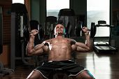 stock photo of pectorals  - Handsome Young Man Doing Dumbbell Incline Bench Press Workout In Gym - JPG