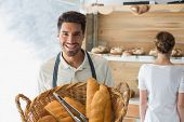 Portrait of a happy confident young waiter with basket of breads at the coffee shop