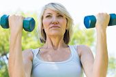 picture of lifting-off  - Closeup of sporty woman lifting dumbbells in the park - JPG