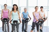Group of happy women working out at elliptical class in gym