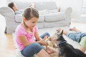 Siblings lying on rug with their yorkshire terrier at home in the living room