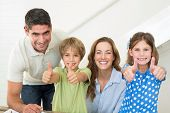Portrait of happy family showing thumbs up at home