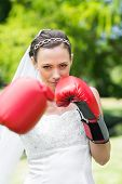 Portrait of confident young bride with boxing gloves punching in garden