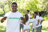 Portrait of happy volunteer holding tshirt with friends disucssing in background