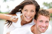 Happy couple on beach having fun piggyback ride in love outdoor smiling happy laughing together on romantic holidays vacation travel trip. Young multiracial people, Asian woman, Caucasian man, 20s.