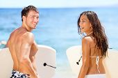 Surfers on beach having fun in summer. Surfer woman and man with boogieboard smiling happy on beach