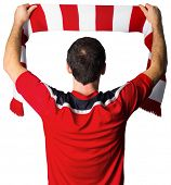 Football fan in red holding scarf on white background