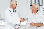 Smiling senior patient and doctor shaking hands in the medical office