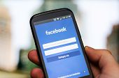 Hand Holding Phone With Facebook Social Network Mobile