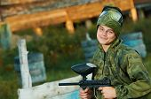 Happy paintball sport player man in protective camouflage uniform and mask with marker gun outdoors