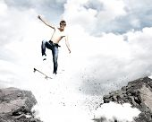 Skater in jeans jumping over mountain gap