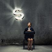 Young businesswoman sitting on chair and looking at dollar symbol above