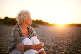 pic of retirement age  - Old woman sitting on the beach looking away at copyspace - JPG