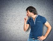 Man Making Silence Gesture Over Textured Background