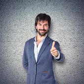 Handsome Man With Thumb Up Over Textured Background