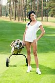 Attractive brunete golfer girl on golf course