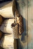 foto of baste  - Ancient russian bag from bast in wooden house - JPG