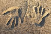 Two Opposite Handprints In The Sand