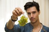 Young Man Holding A Large Delicious Ripe Bunch Of Grapes