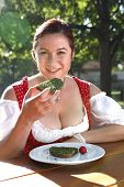 Woman In Typical Bavarian Costume Eats Bread With Chives In A Bavarian Beer Garden