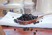 stock photo of dry fruit  - Dried blueberries on rustic wooden spoon in kitchen - JPG
