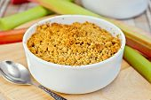 Crumble With Rhubarb In Bowl On Tablecloth And Board