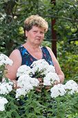 stock photo of meadowsweet  - mature woman with flowers at a garden - JPG