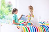 stock photo of pillow-fight  - Two children happy laughing boy and cute curly little girl having fun at pillow fight with feathers in the air jumping laughing and giggling in a white bedroom with colorful bedding - JPG