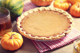 stock photo of pumpkin pie  - Pumpkin pie with small pumpkins on red striped napkin  - JPG