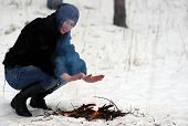 Girl Warms His Hands Over The Fire In Winter