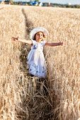 Girl In A White Dress And A Hat Runs On A Wheat Field