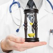 Doctor Holdling In His Hand A Hourglass - Heath Care Concept