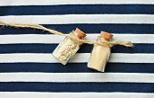 little corked bottles with sand on stripy background